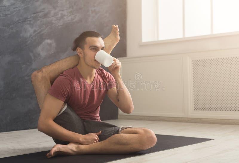 Young man in flexible yoga pose drinking tea royalty free stock photos