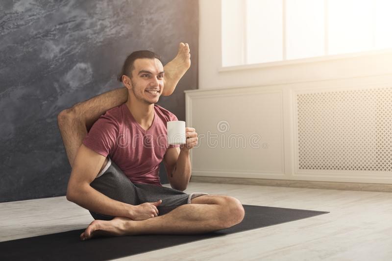 Young man in flexible yoga pose drinking tea stock photo