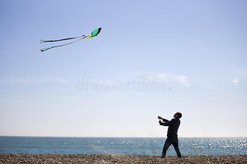 A young man flying a kite on the beach royalty free stock photography