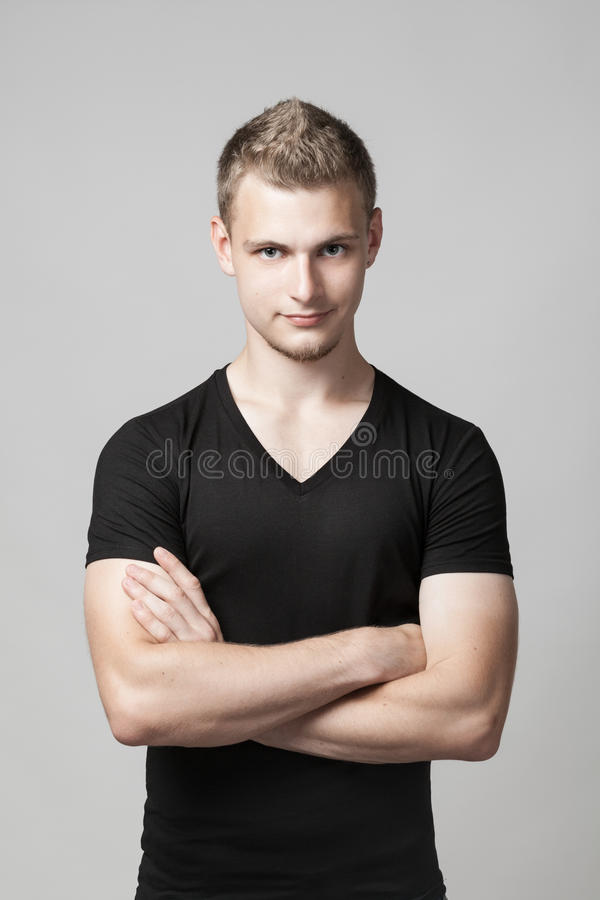 Young man with folded arms on gray royalty free stock photos