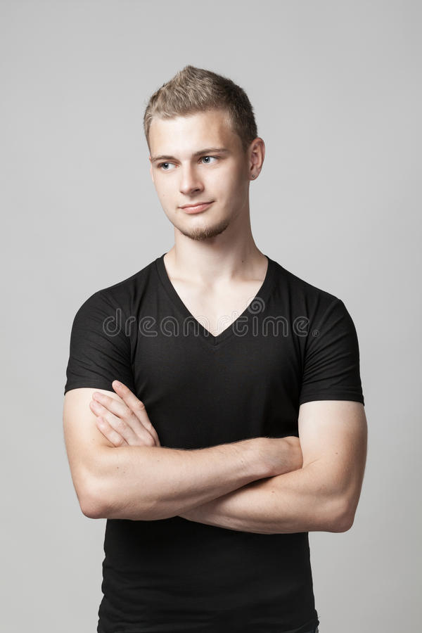 Young man with folded arms isolated on gray stock photography