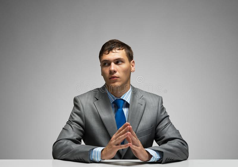 Young man folded hands and having serious face royalty free stock photo