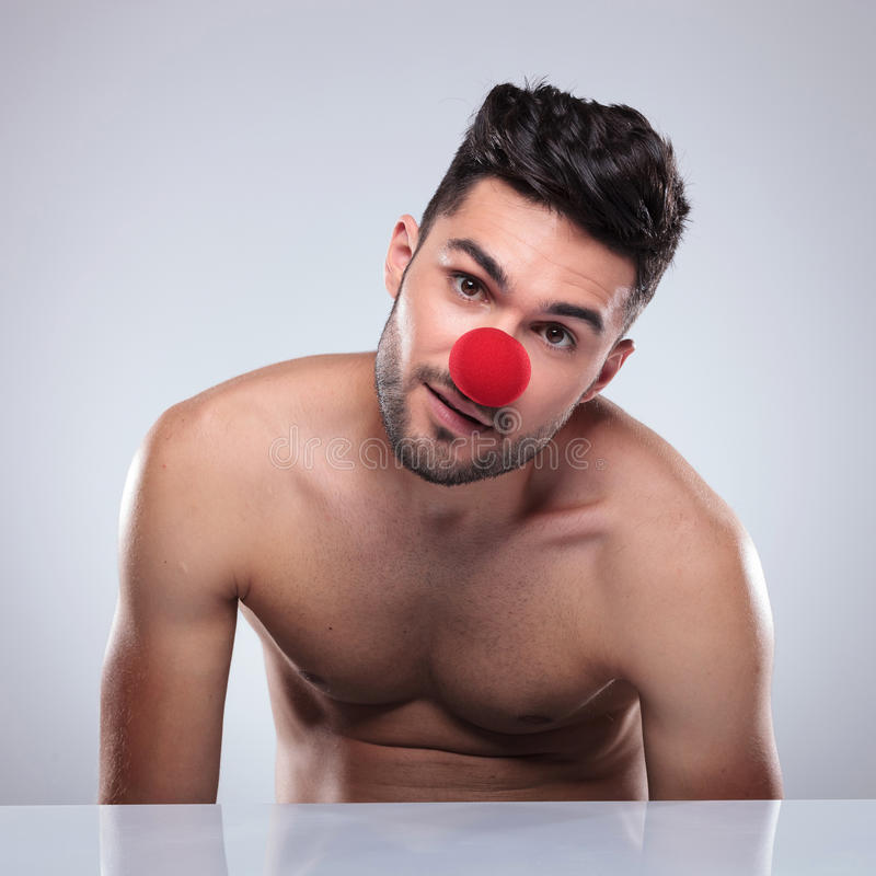 Young man fooling around. Wearing a clown's red nose in studio stock photography