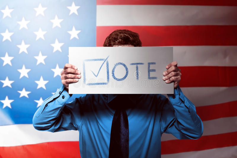 Young man with formal blue shirt holding a card. With vote message text stock photos
