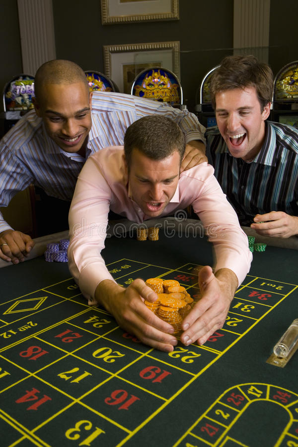 Young man with friends collecting pile of gambling chips from roulette table in casino, smiling stock photography