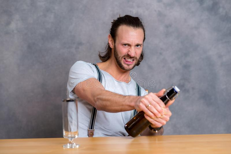 Young man opening a beer bottle royalty free stock photography