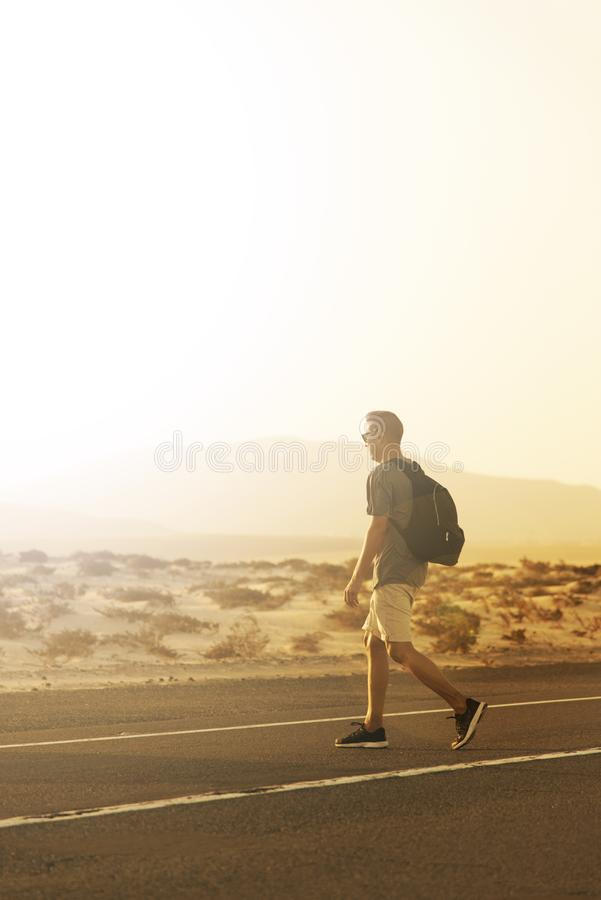 Young man in Fuerteventura, Spain. A young caucasian man, wearing shorts and carrying a backpack, crosses the road, at the Corralejo dunes in Fuerteventura royalty free stock photography