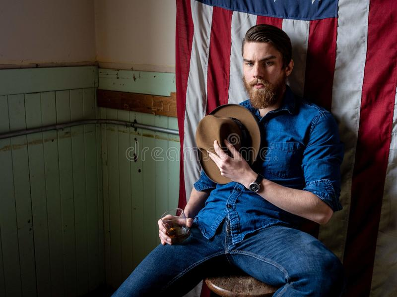 Man with beard sitting against an American flag in a dirty room royalty free stock photography