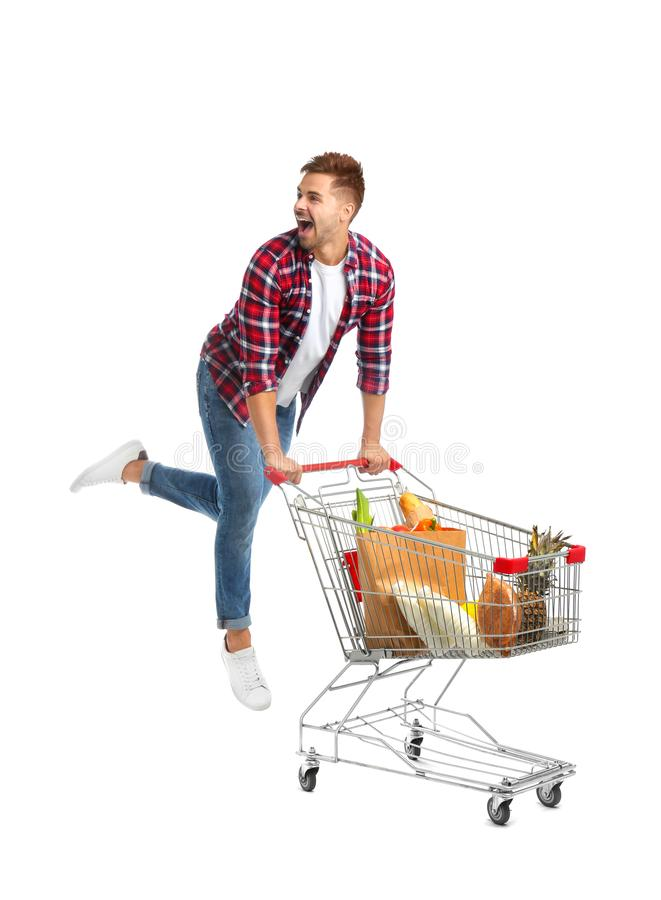 Young man with full shopping cart on  background. Young man with full shopping cart on white background stock photo