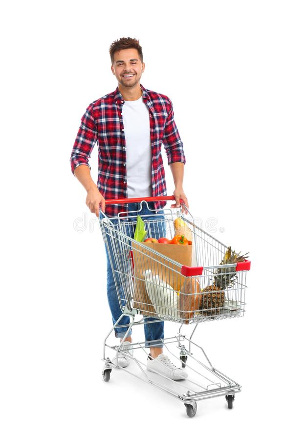 Young man with full shopping cart on background. Young man with full shopping cart on white background stock photos