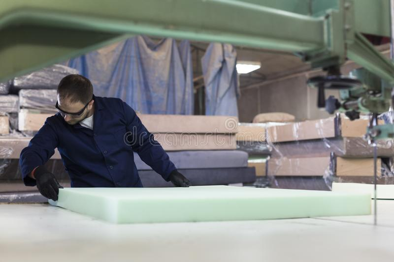 Young Man In A Furniture Factory Is Cutting The Foam For ...