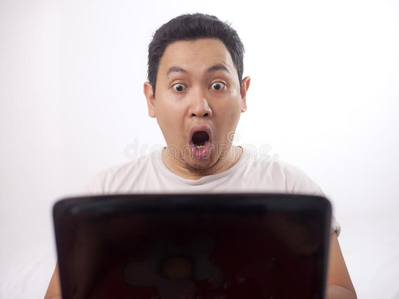 Young Man Gasping, Shocked Expression Looking at Laptop. Young Asian man wearing white shirt gasping, shocked expression looking at his laptop. Close up body royalty free stock photography