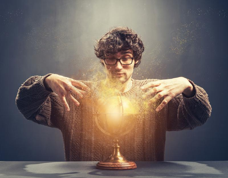 Young man gazing at the glowing crystal ball. Predicting the future. Crystal gazing. Magic stock images