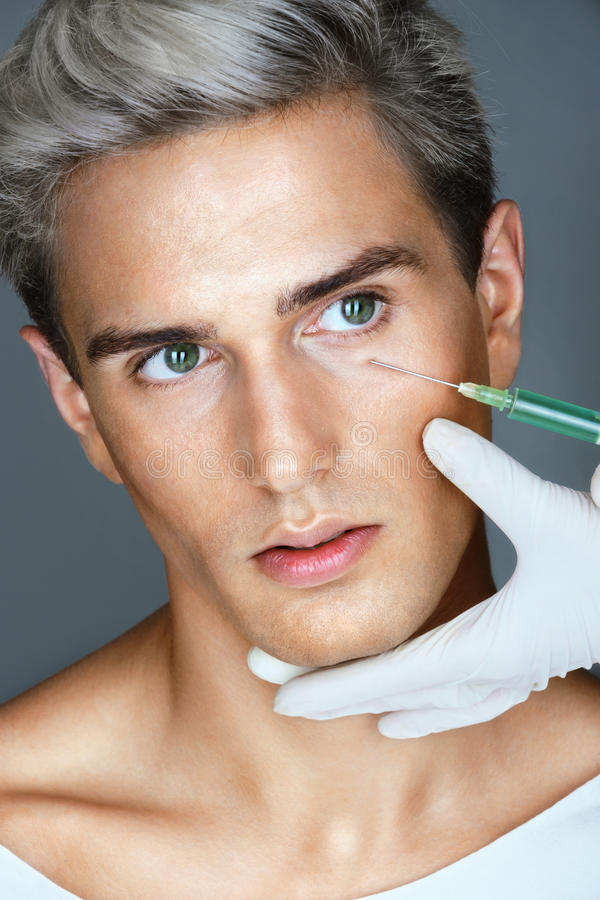 Young man gets Botox injection in eye area from doctor. royalty free stock images