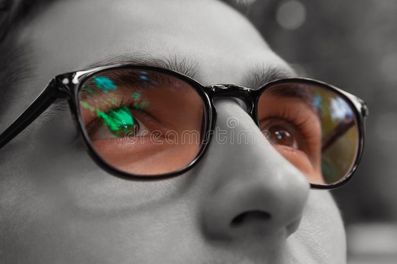 Young man gets colorful bright sight wearing glasses. Eyewear to improve vision. Close up of eyes. Young man gets colorful bright sight wearing glasses. Eyewear royalty free stock photos