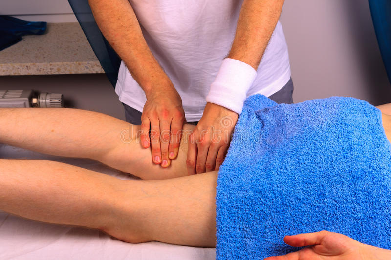 Young man gets thigh massage royalty free stock images