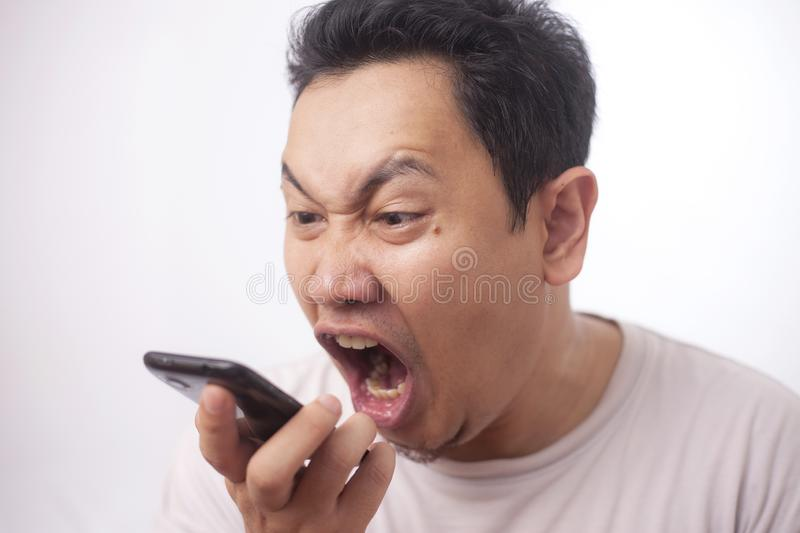 Young Man Getting Bad News on Phone, Shocked and Angry stock photo