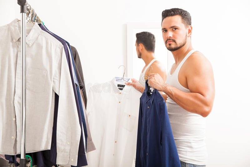 Young man getting dressed in his bedroom. Attractive and strong young man choosing between to shirts to wear while getting dressed in a dressing room stock image