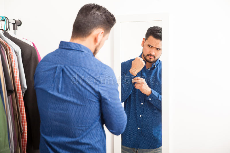 Young man getting dressed and looking good. Portrait of a handsome young Hispanic man getting dressed on casual clothes in front of a mirror royalty free stock photography