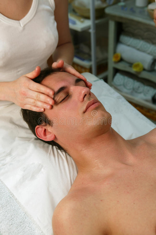 Young man getting a face massage stock photography