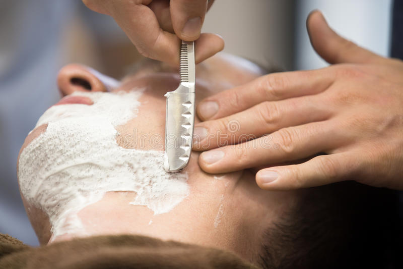 Young man getting a shave with straight razor royalty free stock photo