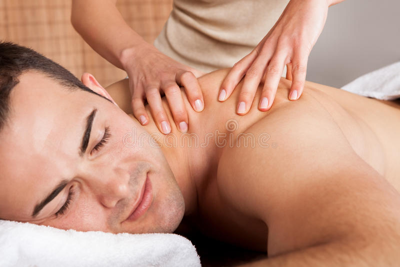 Young man getting shoulder massage stock photography