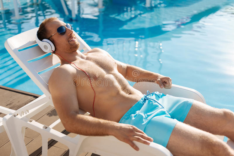 Young man getting a tan on chaise longue stock image