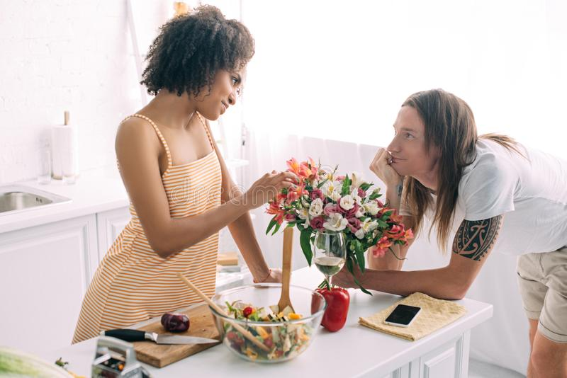 young man gifting bouquet of flowers to african american girlfriend royalty free stock image