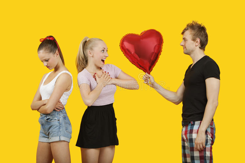 Young man gifting heart shaped balloon to surprised woman with friend feeling left out standing behind royalty free stock image
