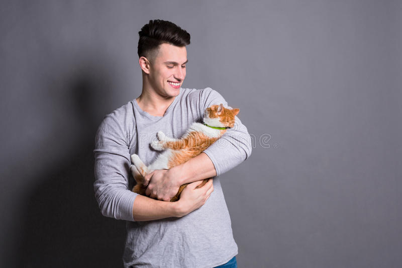 Young man with ginger cat at gray studio background. Young man with ginger cat. Pet care, positive emotion concept at gray studio background royalty free stock photos