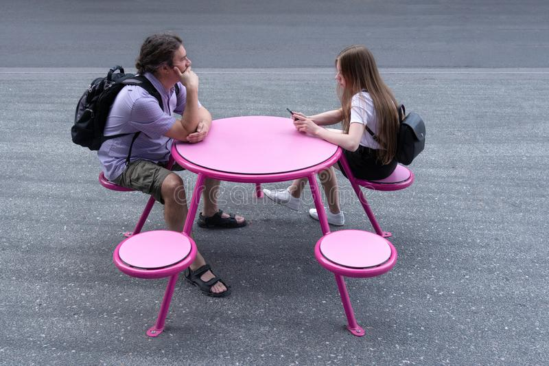 A young man and girl are sitting at a pink table in the street stock images