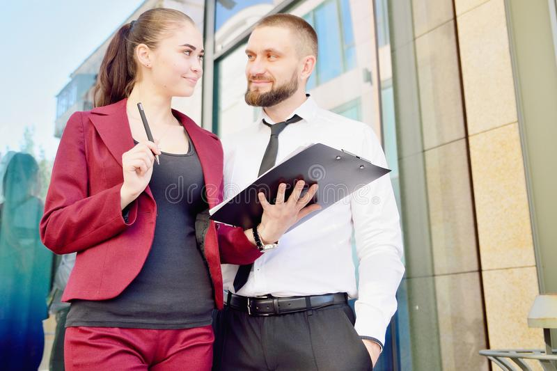 Young man and girl in white shirts with a tablet on the background of an office building. Office workers. royalty free stock image