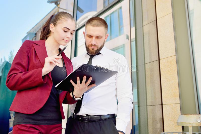 Young man and girl in white shirts with a tablet on the background of an office building. Office workers. royalty free stock photo