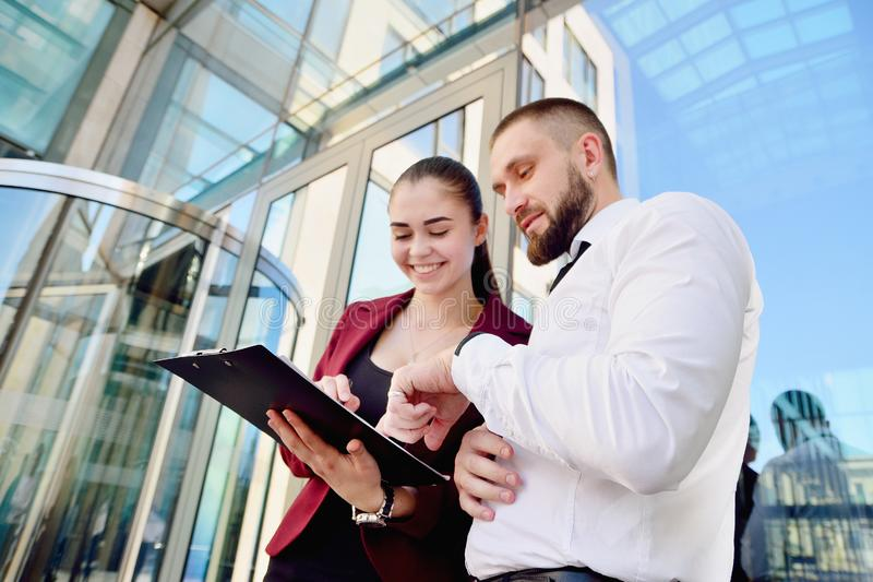 Young man and girl in white shirts with a tablet on the background of an office building. royalty free stock image