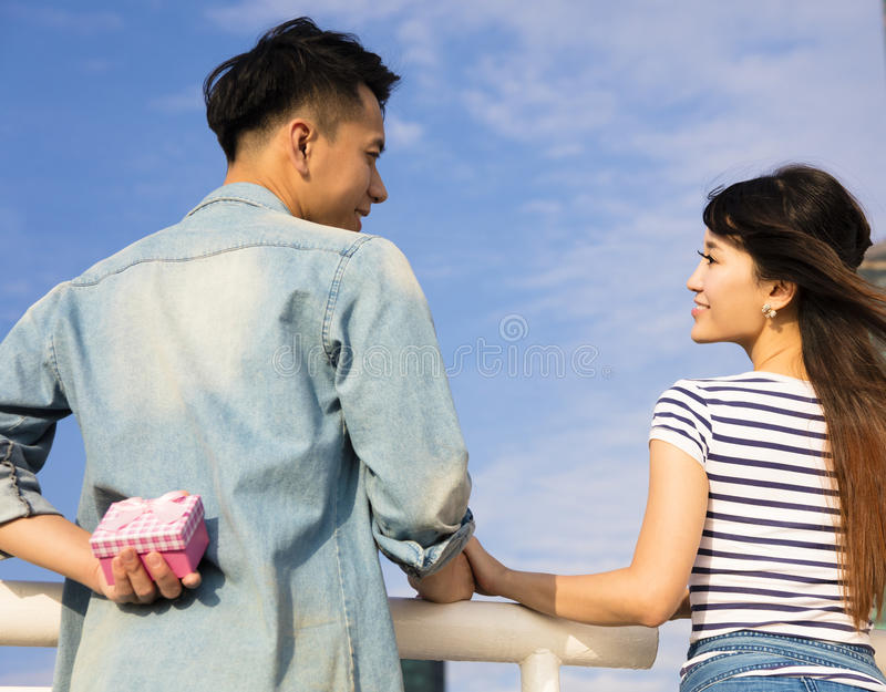 Young man gives a gift to girlfriend. Happy young men gives a gift to girlfriend royalty free stock photography