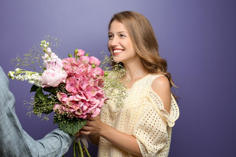 Young man giving beautiful flowers to his beloved girlfriend on color background royalty free stock photo