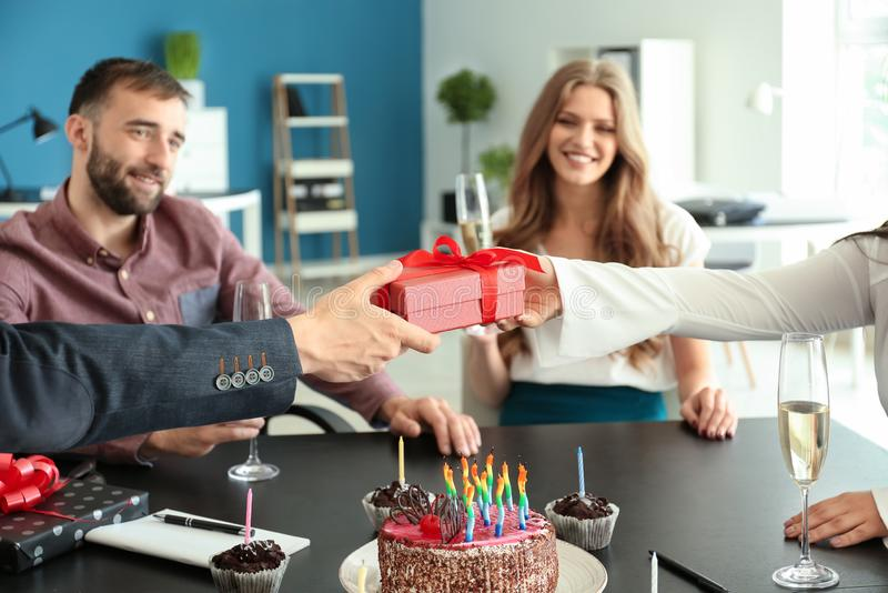 Young man giving birthday present to his colleague at party in office stock photos