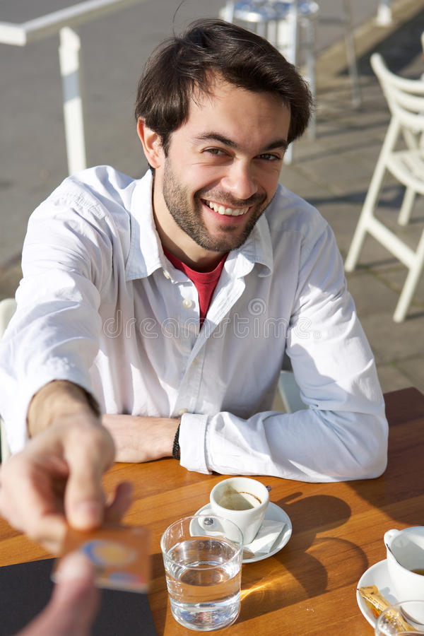 Young man giving credit card for payment at restaurant royalty free stock images