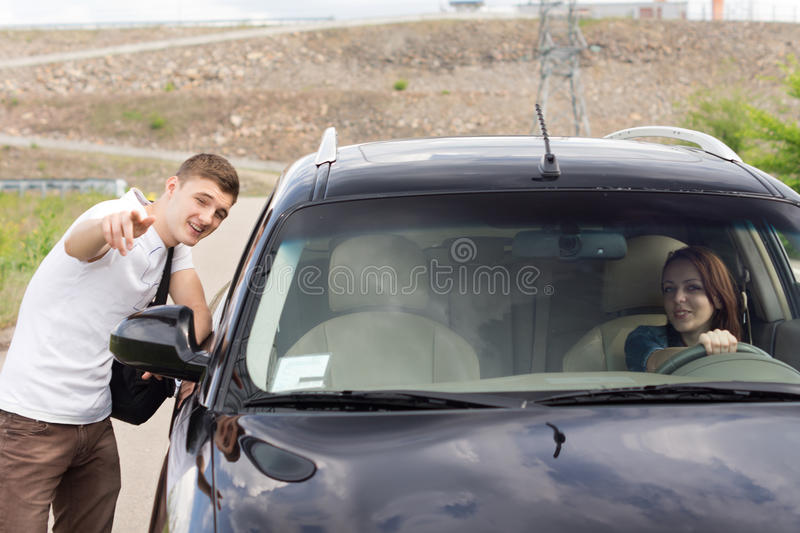 Young man giving directions to a woman driver stock photography