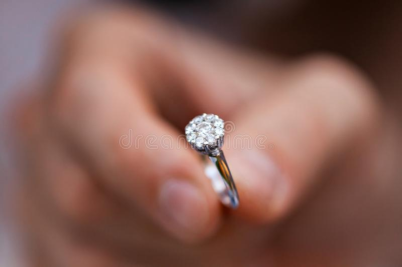 Close-up of a ring in a mans hand. young man giving engagement ring to his girlfriend. Man making marriage proposal to royalty free stock photos