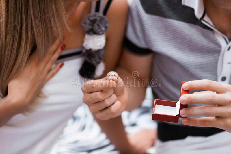 Young man giving engagement ring to his girlfriend. Man making marriage proposal to his beloved woman. Romantic date. stock image