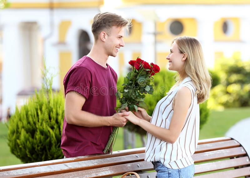 Young man giving flowers to his girlfriend on romantic date outdoors stock image