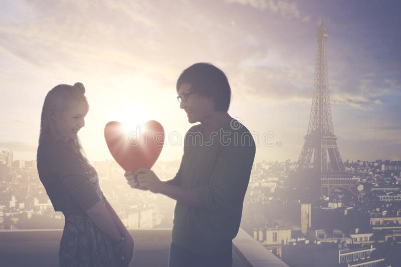 Young man giving a gift to his girlfriend. Image of young men giving a gift shaped heart to his girlfriend while standing on the rooftop with Eiffel tower stock image