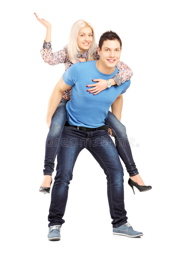 Young man giving his girlfriend a piggy back ride royalty free stock image