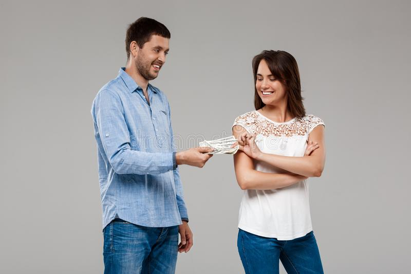 Young man giving money to woman, smiling over grey background. royalty free stock photos