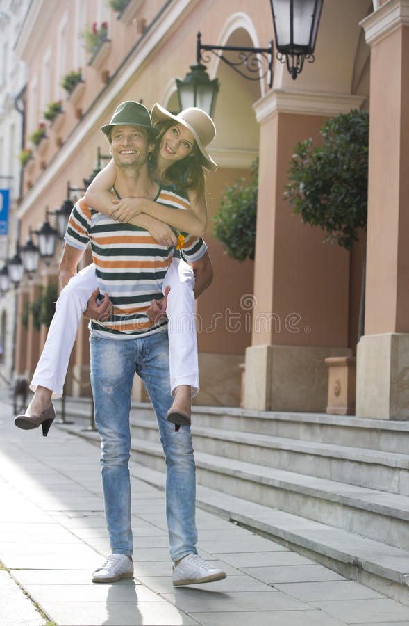 Young man giving piggyback ride to woman on sidewalk by building royalty free stock photo