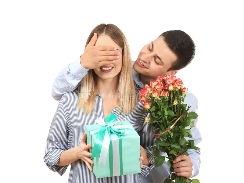 Young man giving present and flowers to his beloved girlfriend on white background stock image