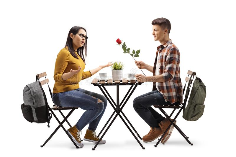 Young man giving a present to a happy young woman at a restaurant stock image