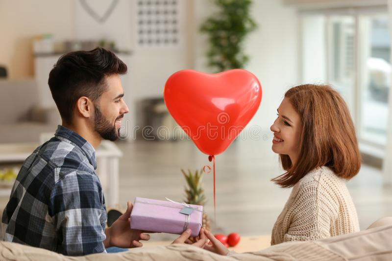 Young man giving present to his beloved girlfriend at home. Celebration of Saint Valentine's Day royalty free stock image