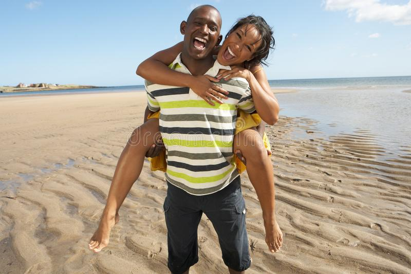 Download Young Man Giving Woman Piggyback Along Shoreline Stock Image - Image of happy, mixed: 13673357